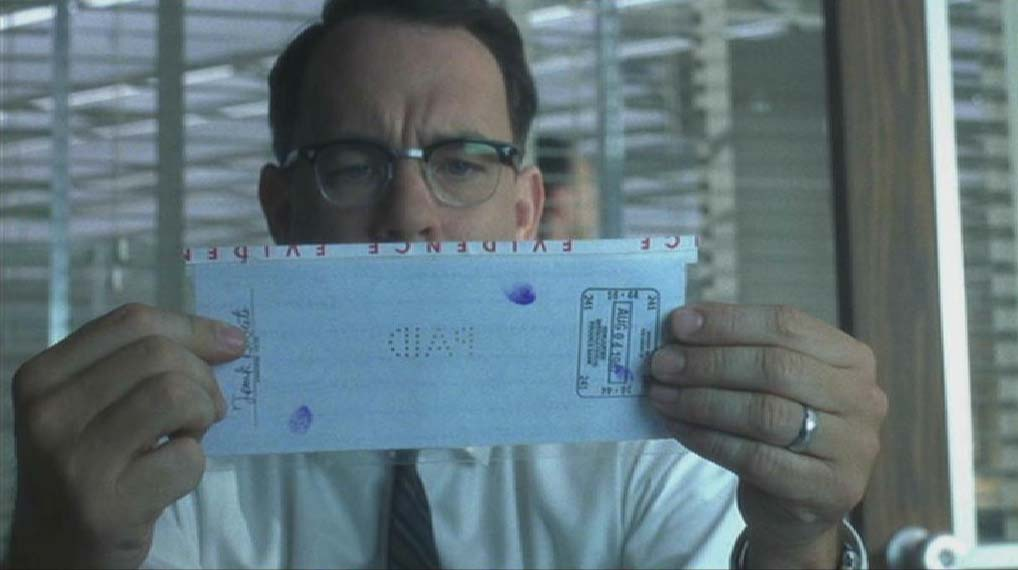 F.B.I. agent Carl Hanratty studies perforated check